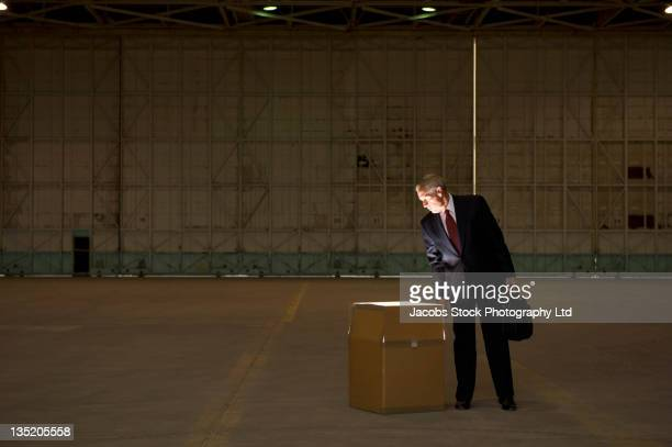 Caucasian businessman looking into glowing box in warehouse
