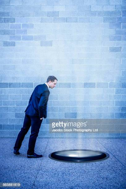 Caucasian businessman looking into glowing hole
