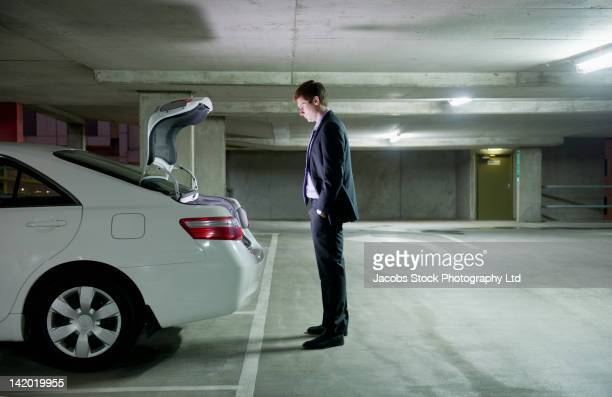 Caucasian businessman looking into trunk of car