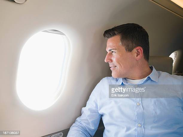 Caucasian businessman looking out airplane window