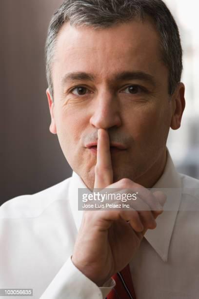 Caucasian businessman making shhh gesture