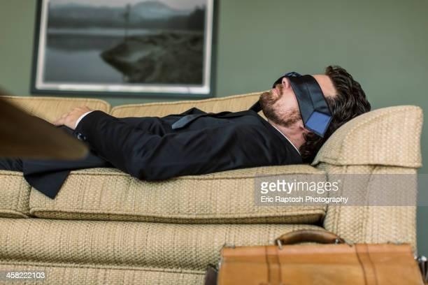 Caucasian businessman napping on sofa