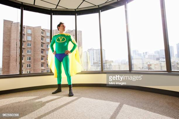 A Caucasian businessman office super hero stands at an office window and ponders his next business move.