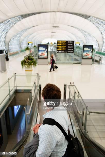 Caucasian businessman on escalator in airport
