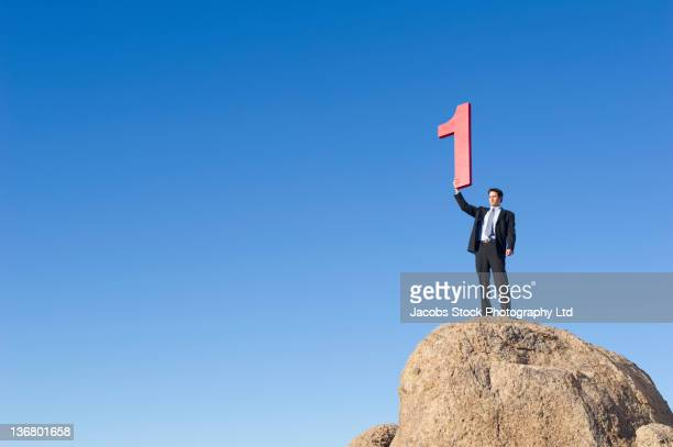Caucasian businessman on rock lifting large number 1