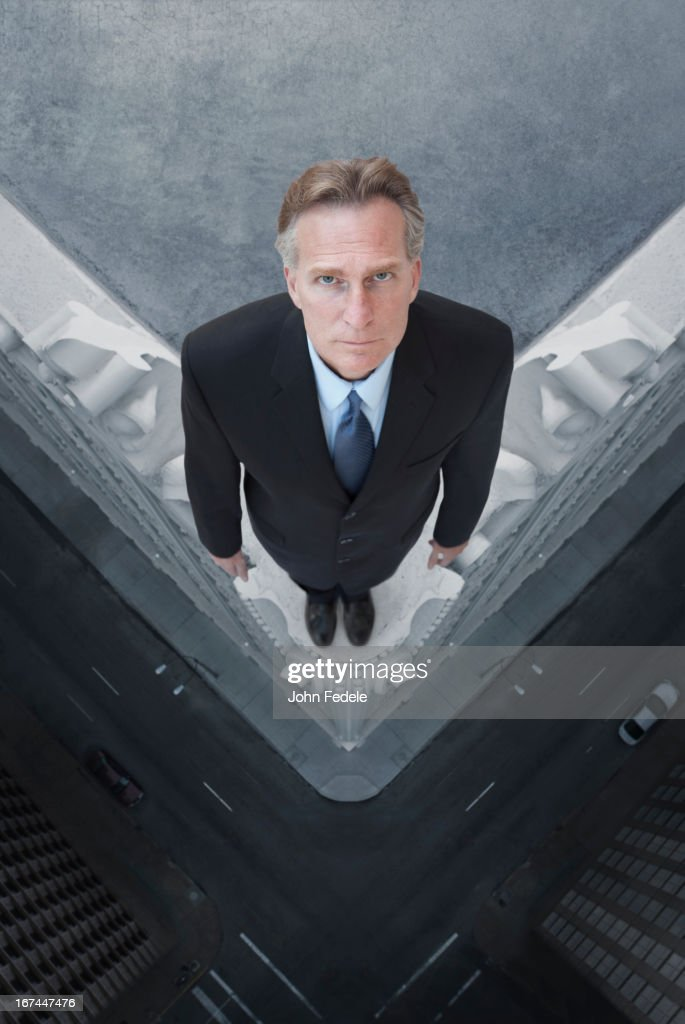 Caucasian businessman on skyscraper ledge : Stock Photo