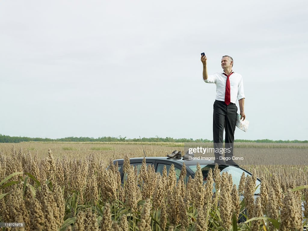 Caucasian businessman on top of car in field looking at gps device : Stock Photo
