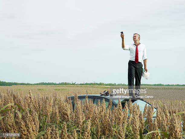 caucasian businessman on top of car in field looking at gps device - lost stock pictures, royalty-free photos & images