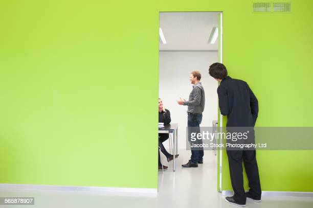 Caucasian businessman peeking in at office meeting