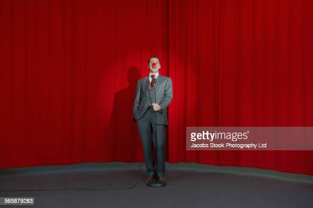 caucasian businessman performing comedy on stage - clown's nose stock photos and pictures
