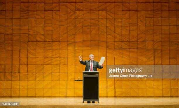 caucasian businessman practicing speech in empty auditorium - zuschauerraum stock-fotos und bilder