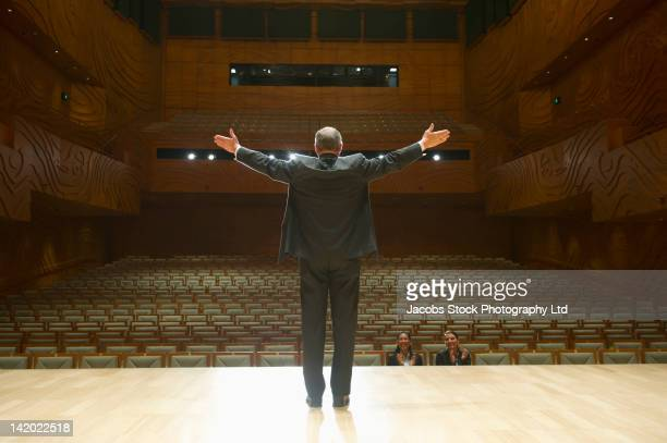 Caucasian businessman practicing speech in empty auditorium