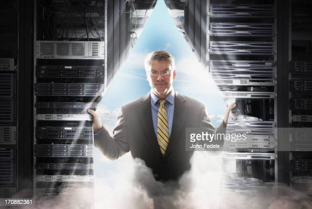 Caucasian businessman pulling back curtain to clouds