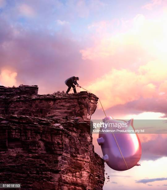 caucasian businessman pulling large piggy bank up cliff - big bulge stock pictures, royalty-free photos & images
