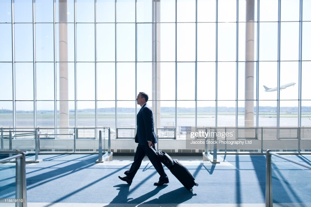 Caucasian businessman pulling luggage in airport : Stock Photo