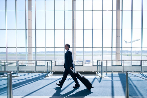 Caucasian businessman pulling luggage in airport - gettyimageskorea
