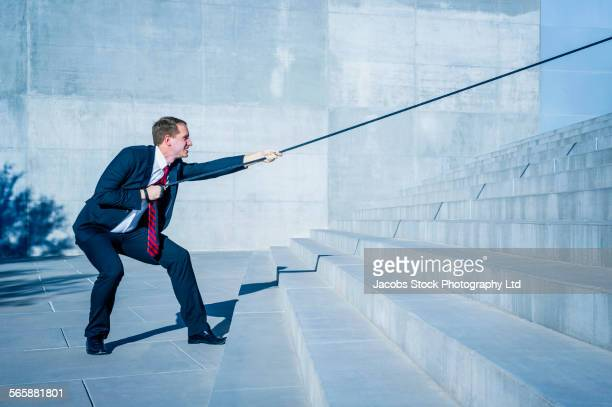 Caucasian businessman pulling rope down outdoor staircase