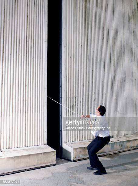 Caucasian businessman pulling rope from warehouse building