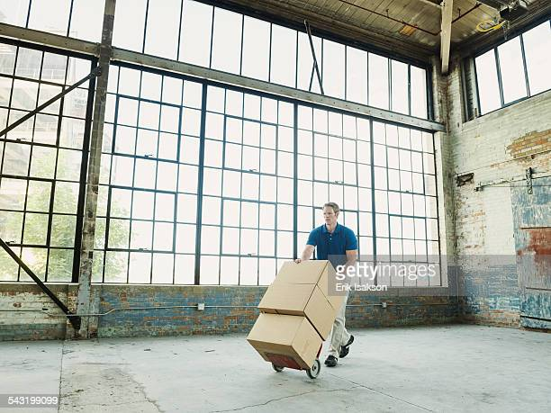 Caucasian businessman pushing cardboard boxes on hand truck in warehouse