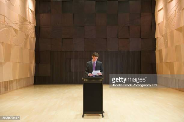 Caucasian businessman reading at podium on stage