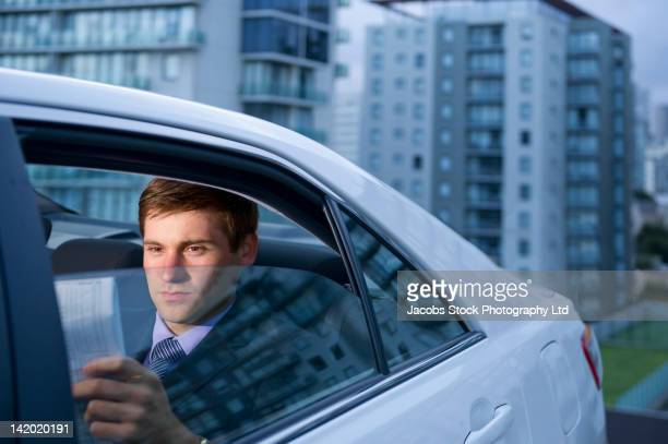 Caucasian businessman reading in back seat of car
