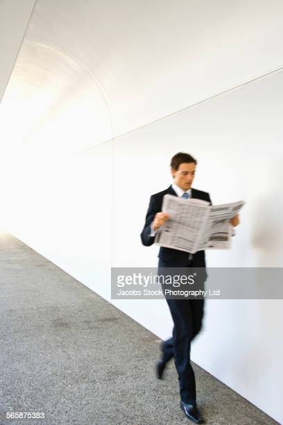 Caucasian businessman reading newspaper while walking