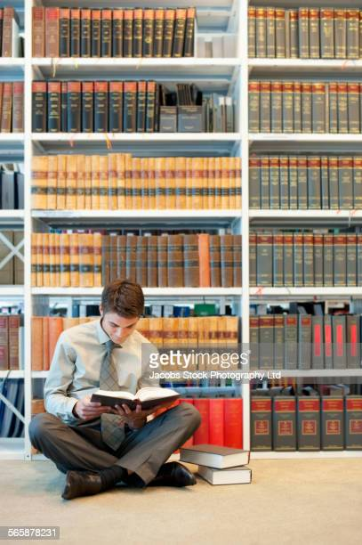 caucasian businessman reading on floor in law library - legal system stock pictures, royalty-free photos & images