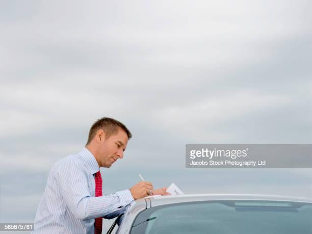 Caucasian businessman reading paperwork on car