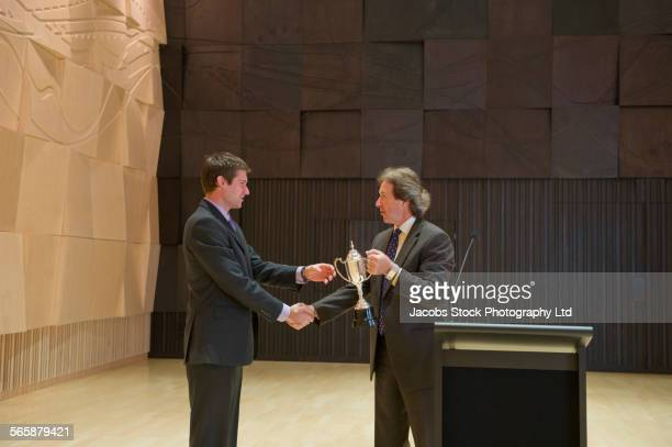 Caucasian businessman receiving trophy and handshake