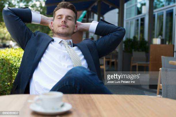 Caucasian businessman relaxing at cafe outdoors