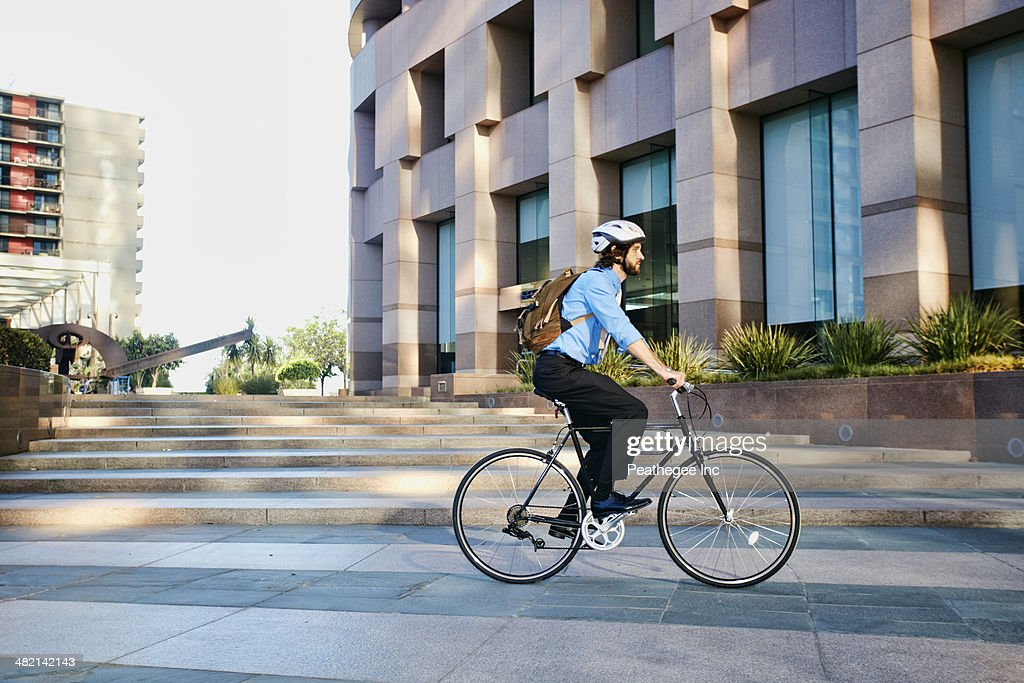 Caucasian businessman riding bicycle outside office building : Stock Photo