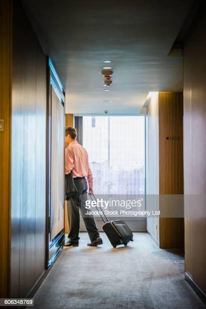 Caucasian businessman rolling luggage in hotel hallway