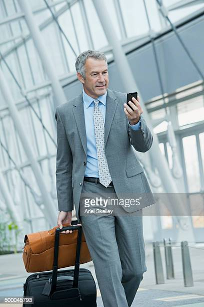 Caucasian businessman rolling luggage in lobby