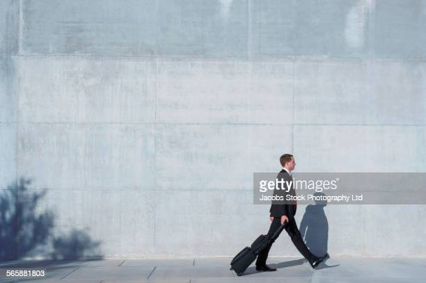 Caucasian businessman rolling luggage near concrete wall