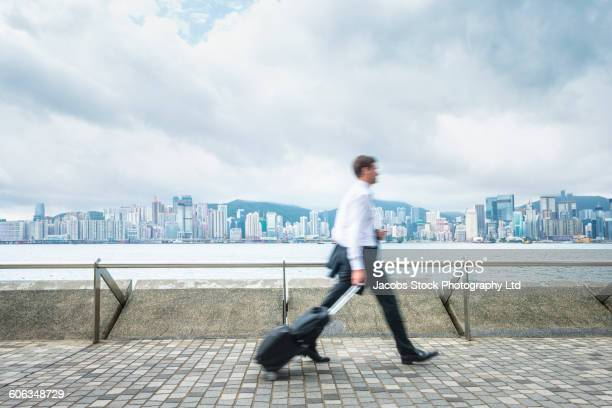 Caucasian businessman rolling luggage on waterfront