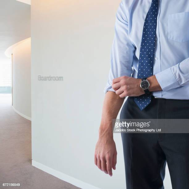 caucasian businessman rolling up sleeve - 袖を折った袖まくり ストックフォトと画像