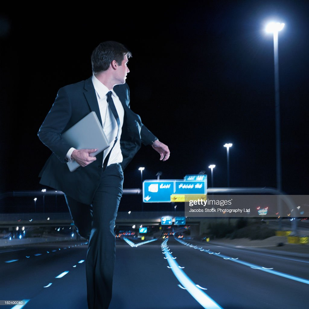 Caucasian businessman running on urban freeway at night : Stock Photo