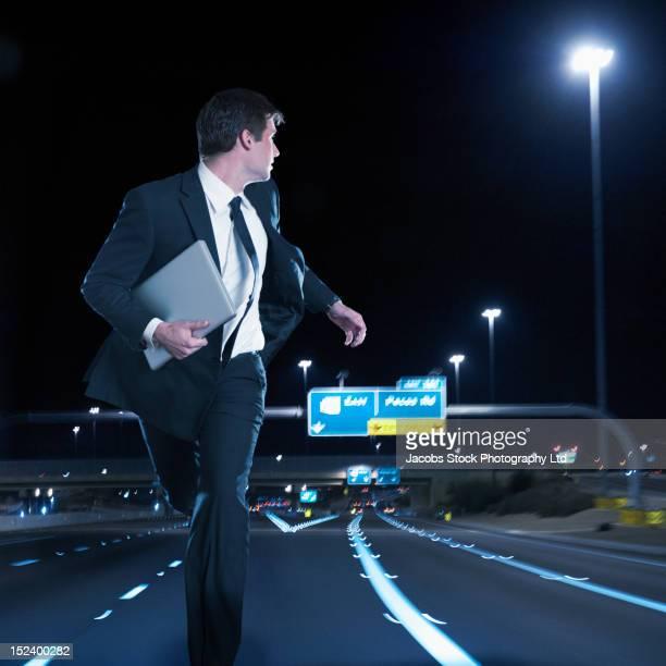 Caucasian businessman running on urban freeway at night