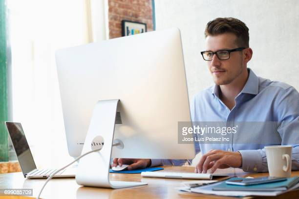 Caucasian businessman sitting at desk using laptop