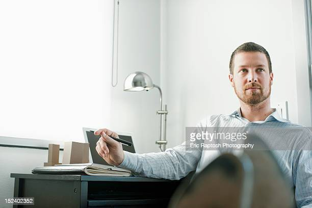 Caucasian businessman sitting at desk with feet up