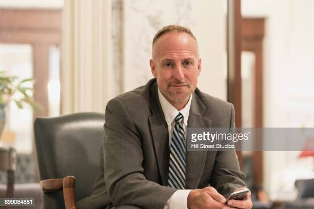 Caucasian businessman sitting in armchair holding cell phone