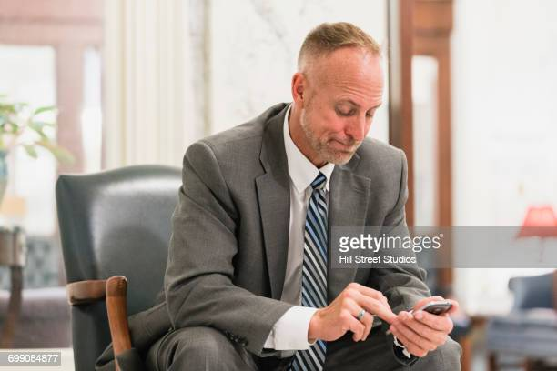 caucasian businessman sitting in armchair texting on cell phone - tensed idaho stock photos and pictures