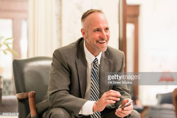 Caucasian businessman sitting in armchair texting on cell phone