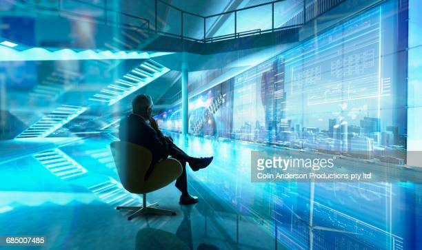 Caucasian businessman sitting in chair in futuristic office