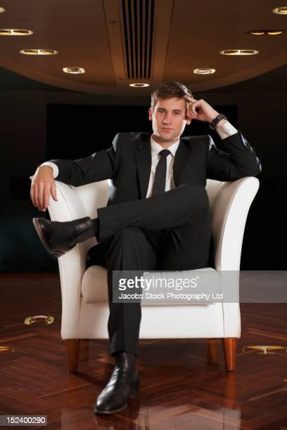 Caucasian businessman sitting in chair thinking