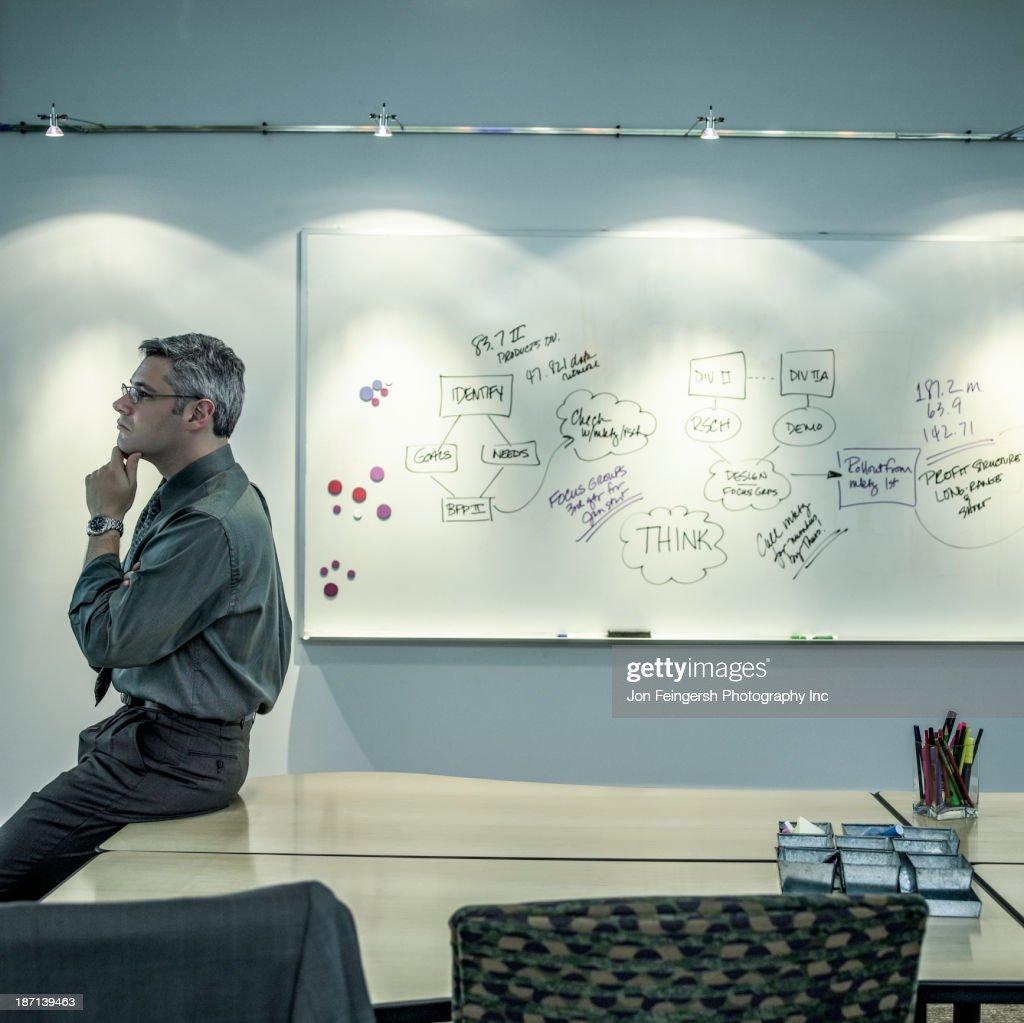 Caucasian businessman sitting on desk : Stock Photo