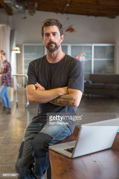 Caucasian businessman sitting on desk with laptop