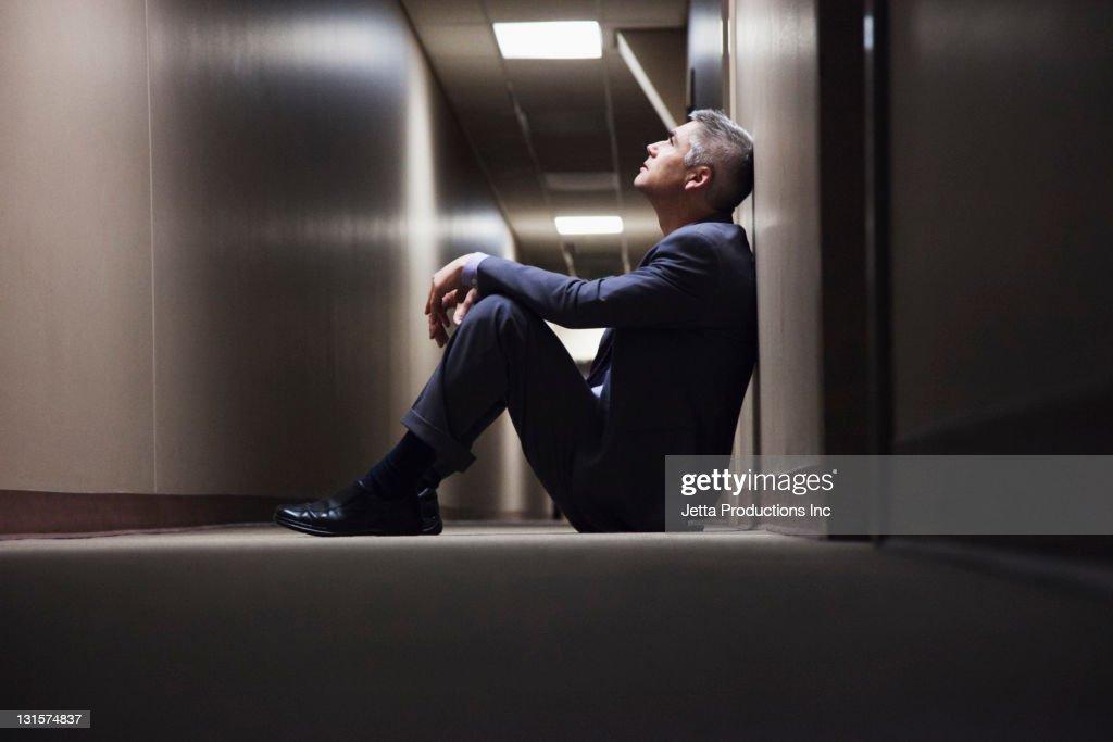 Caucasian businessman sitting on floor in corridor : Stock Photo