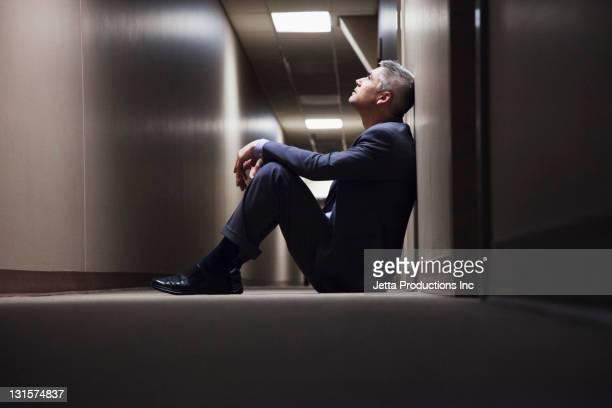 caucasian businessman sitting on floor in corridor - failure - fotografias e filmes do acervo