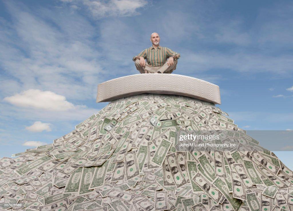 Caucasian businessman sitting on mattress on mountain of money : Stock-Foto